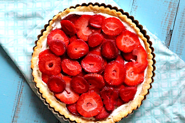Sliced strawberries in a strawberry pie with cream cheese in a tart shell