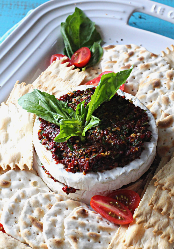 Sun dried Tomato appetizer with basil and garlic stuffed in a wheel of brie cheese surrounded by water crackers.