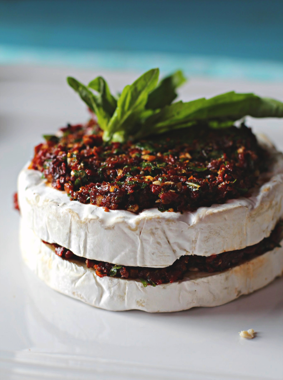 Sun dried tomatoes and basil spread on a wheel of brie cheese and garnished with fresh basil