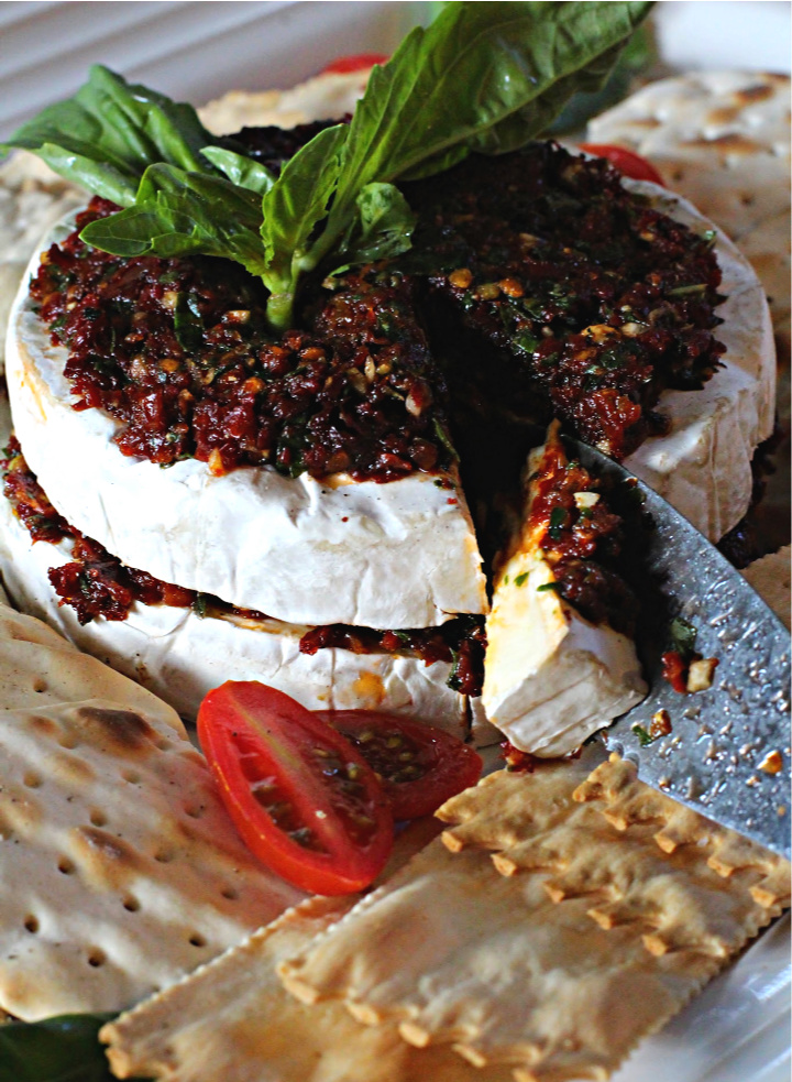 Two halves of a wheel of brie cheese topped with sun-dried tomatoes in oil and served with water crackers and garnished with fresh basil leaves