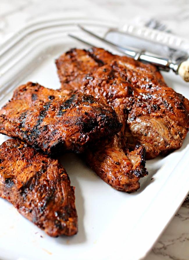 Grilled pork steaks on a white platter for tacos al pastor