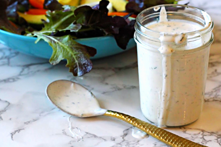 Homemade buttermilk ranch dressing served in a mason jar with a tossed salad.