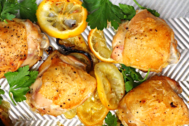 Crispy baked lemon chicken thighs on a sheet pan with lemon slices and pieces of fresh parsley