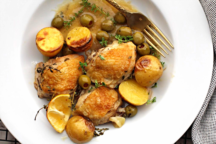 Crispy chicken thighs oven roasted with potatoes, olives and lemons. Served in a wide shallow white bowl.