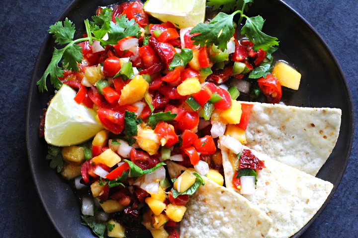 Spicy peach salsa on a dark gray plate served with tortilla chips and limes.
