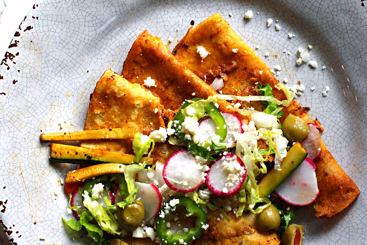 Red chile enchiladas topped with strips of zucchini, radish, sliced jalapenos, green olives, sliced romaine lettuce.
