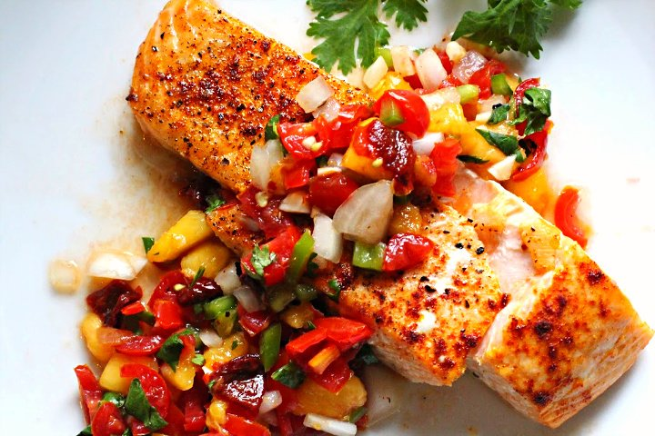 Spicy peach salsa served over a salmon fillet that's been seasoned with salt pepper and smoked paprika