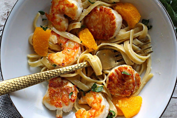 Seared shrimp scallops with fettuccini noodles in an orange cream sauce topped with orange slices and fresh basil.
