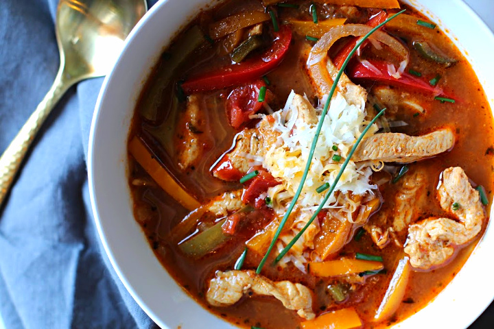 Chicken fajita soup topped with grated Mexican cheese, served in a white soup bowl with a bowl full of tortilla strips for garnish.