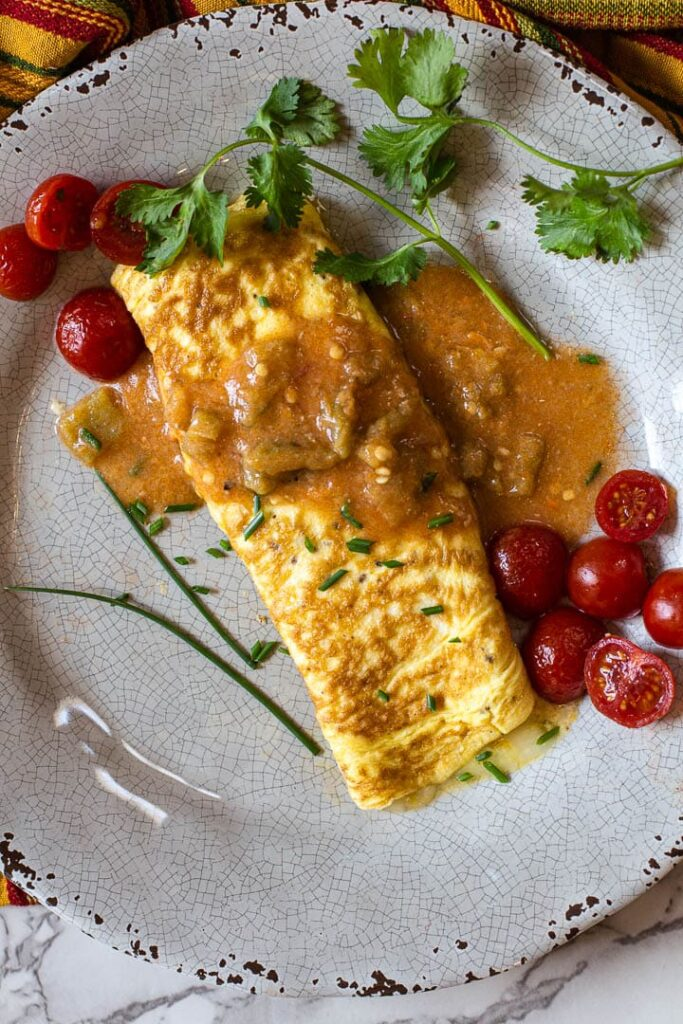 Cheese Omelette smothered in hatch green chile sauce and garnished with cherry tomatoes and cilantro