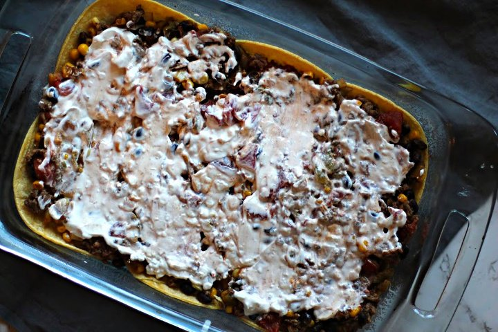 Layered Mexican Casserole with Ground Beef and Corn tortillas topped with sour cream.