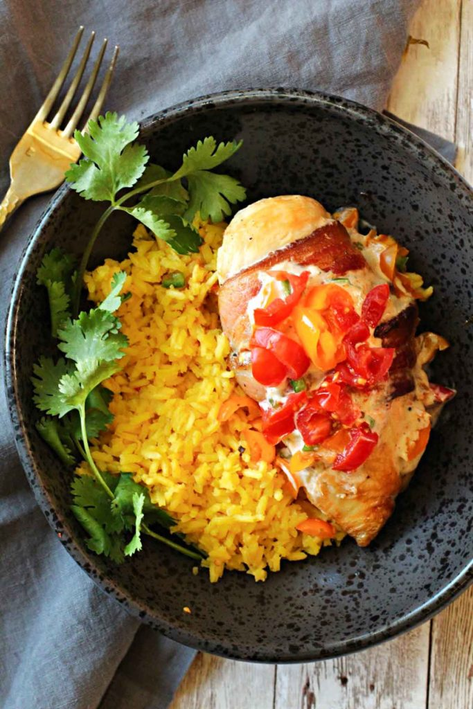 Mexican spiced chicken wrapped in bacon and topped with a chipotle cream sauce and tomato salsa. Served with yellow rice and cilantro. Served in a World Market rustic dark grey bowl.