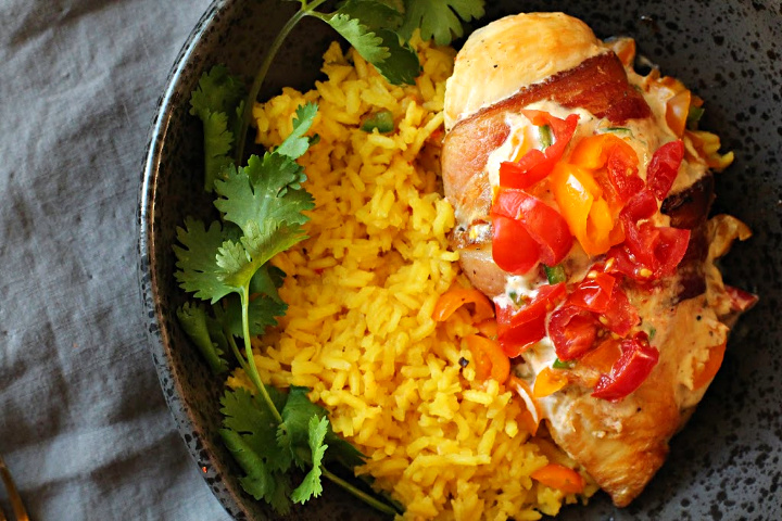 Spicy Mexican Chicken breast wrapped in bacon served with yellow rice and garnished with cilantro. Topped with lemon cream sauce and chopped tomatoes.