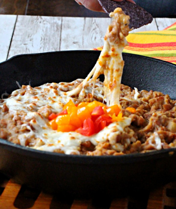 Refried beans in a cast iron skillet topped with cheese and used as a dip appetizer