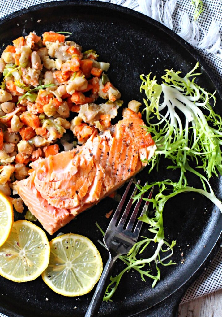 Salmon fillets cooked in a cast iron skillet with Spring vegetable ragout, frizee lettuce and lemon slices