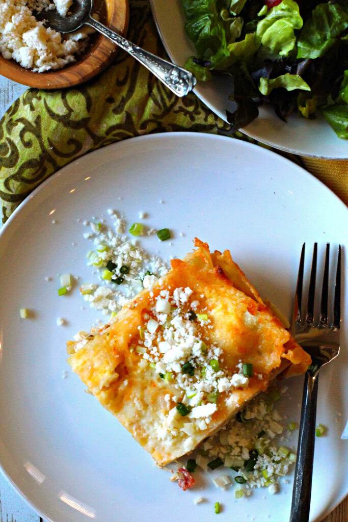 Green Chile Chicken Lasagna served on a white plate sprinkled with cotija cheese and green onions with a tossed green salad.