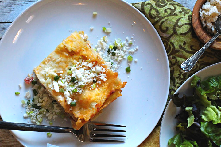 White chicken lasagna served on a white plate sprinkled with cotija cheese and green onion. With a side tossed green salad on the side.