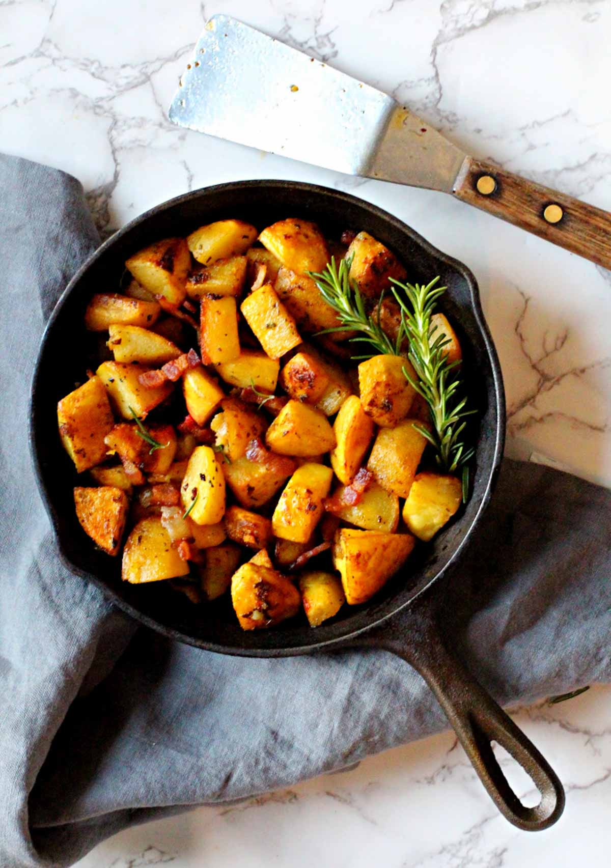 Cubed potatoes cooked in a cast iron skillet with rosemary