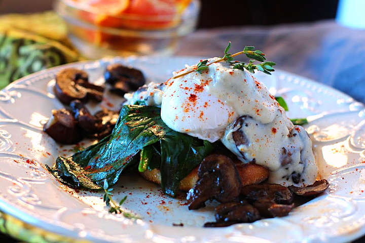 Poached eggs on top of a toasted English Muffin and spinach and topped with Mushroom cream gravy and garnished with additional mushrooms and paprika.