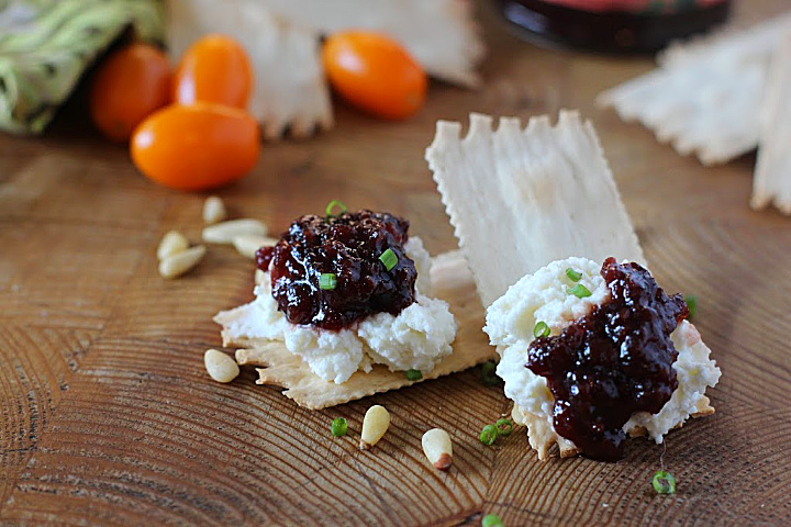 Wafer crackers topped with whipped goat cheese and Heidi's red chile raspberry jam. Placed on a wood cutting board
