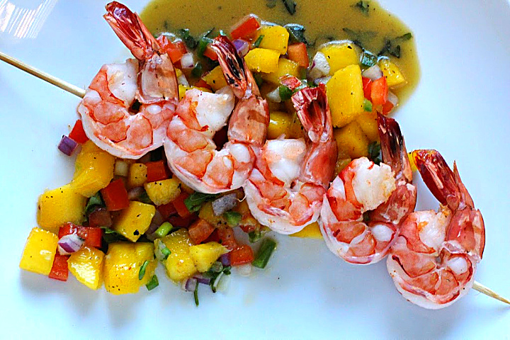 Oven roasted shrimp on wooden skewers served over Mango Salsa with Honey Mustard Basil Vinaigrette