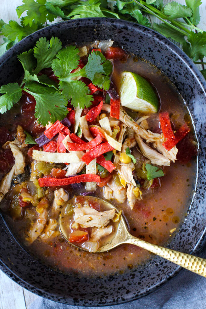 Chicken tortilla soup served in a black bowl garnished with tortilla strips cilantro and lime.