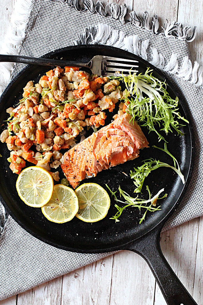 Coho Salmon cooked in a cast iron skillet with diced carrots, celery, shallots and white beans. Garnished with lemon slices and frisee lettuce.