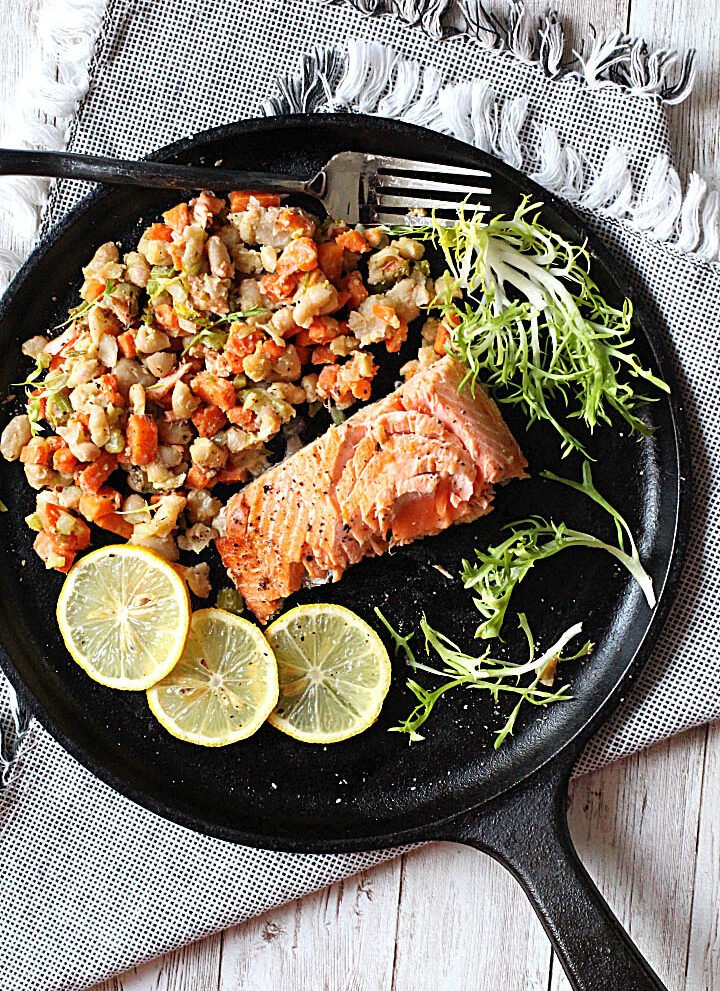 Coho salmon on a cast iron skillet with mixed vegetables ragout and lemon slices