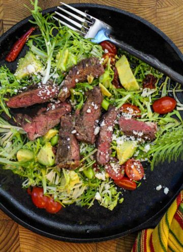 Seared skirt steak on frisee garnished with tomatoes, chopped avocado and cotija cheese. With chipotle dressing