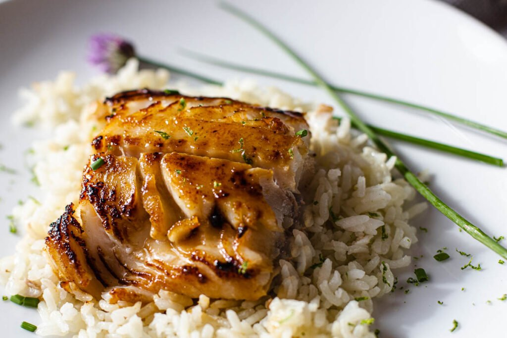 Sablefish black cod with miso glaze served on coconut rice and garnished with fresh chives