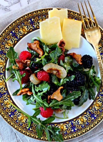 Arugula berry salad with warm chanterelles mushrooms recipe. With cheddar cheese