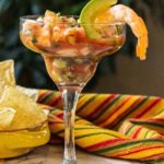 Campechana Mexican Shrimp Cocktail served in a margarita glass and garnished with shrimp and avocado. Served with corn chips